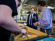 15 APRIL 2019 - DES MOINES, IOWA: JULIÁN CASTRO (center) talks to BEN MALLOY (right), a carpentry teacher, while a student works on a project, during Castro's visit to the Central Campus Skilled Trades Alliance at the Des Moines Public School's Central Campus Monday. Castro is on his third visit to Iowa since declaring his candidacy for the Democratic ticket of the US Presidency. Casto talked to students and administrators about skilled trades education and toured the campus. Iowa traditionally hosts the the first selection event of the presidential election cycle. The Iowa Caucuses will be on Feb. 3, 2020.                PHOTO BY JACK KURTZ