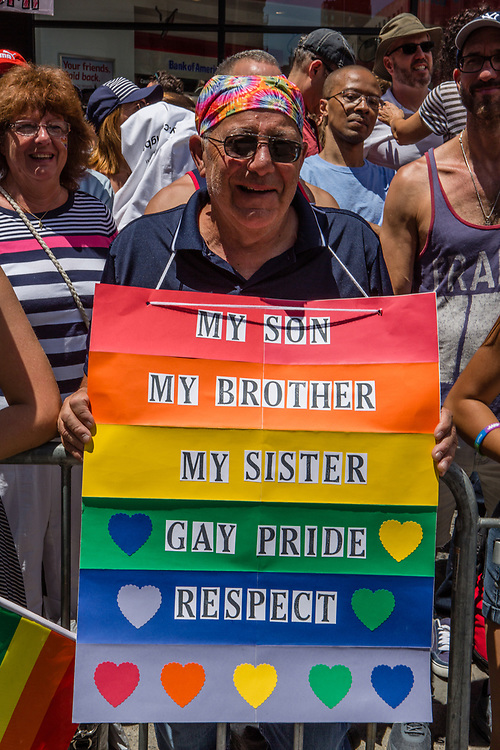 """New York, NY - 25 June 2017. New York City Heritage of Pride March filled Fifth Avenue for hours with groups from the LGBT community and it's supporters. A spectator with a rainbow sign reading """" My son / My brother / My sister / Gay Pride / Respect."""""""