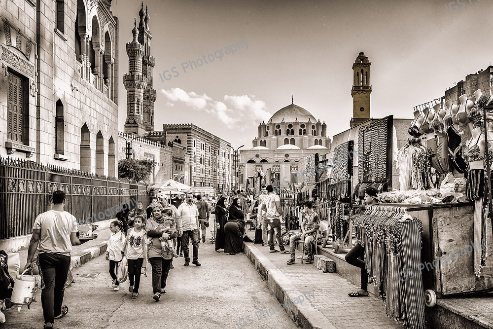 Crowds walking in Azhar Street in front of the main entrance to the Al Azhar Mosque and the Abu Al Dahab mosque in Cairo