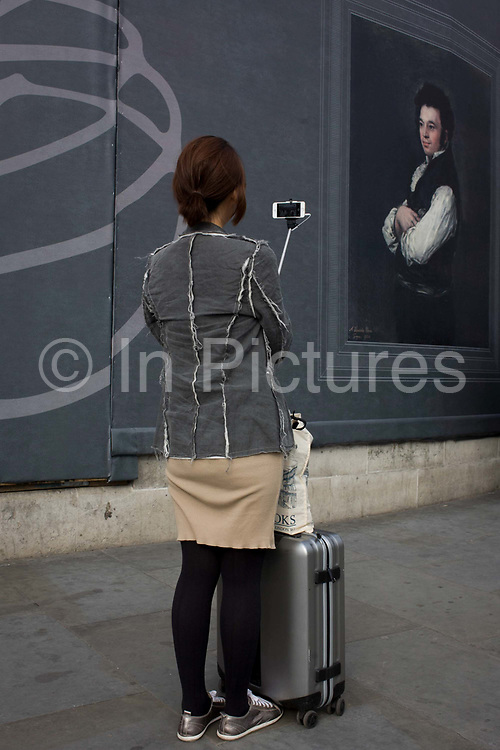 A tourist takes a selfie near a Francesco Goya portrait of Don Tiburcio Pérez y Cuervo, the Architect, sponsored by Credit Suisse and advertised on a construction hoarding outside the National Portrait Gallery. Paintings by the Spanish romantic court artist are being exhibited inside the National Gallery next door and while a large grey hoarding is in place during works in Trafalgar Square, some of Goya's work is reproduced to viewers outside. Tourists to this central landmark in the capital stop and take photos and this selfie girl faces the Goya but seemingly ignores the high art in favour of a fleeting moment with her smartphone - symbolising the disposable and unthinking nature of tourism and travel.