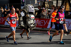 © Licensed to London News Pictures. 03/10/2021. LONDON, UK. A runner in a rhino costume on Embankment passes mile 25 in the London Marathon, the first time it has been held since April 2019 due to the Covid-19 pandemic.  Over 36,000 elite athletes, club runners and fun runners are taking part in the mass event, with another 40,000 people taking part virtually.  Photo credit: Stephen Chung/LNP