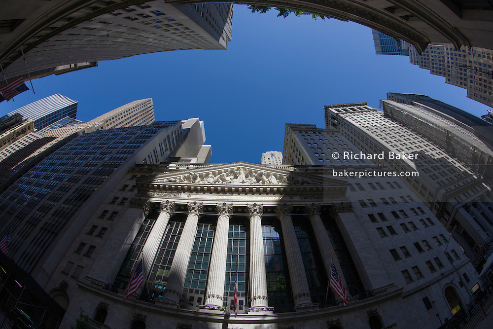 Distorted fish-eye lens view of classical pillars and American flag hanging in front of the New York Stock Exchange (NYSE) on Wall Street, Lower Manhattan,.