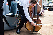 boy tuning his cello for a concert
