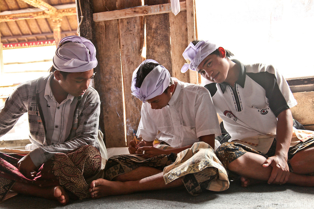 Young Balinese men at a gathering at Ulun Danu Batur temple - an important social and religious center of the area. Bali, Indonesia