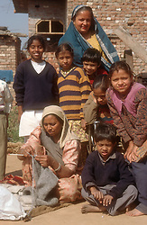 Two women; one knitting; with group of young children together outside brick built house in Punjab; India,