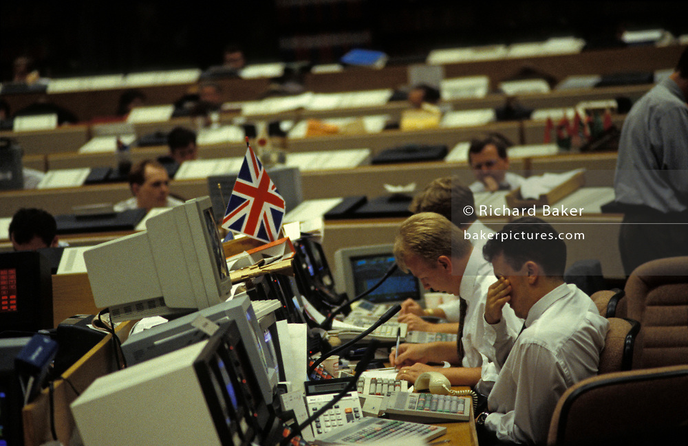A currency banker with the British Union Jack above his desk, rubs tired eyes while working in front of 90s computers in the currency trading floor of National Westminster Bank PLC in the City of London, the capital's financial centre, on 20th May 1992, in London, England. Screens glow with the most up to date trading figures and news items allowing traders to react instantly on the money markets.