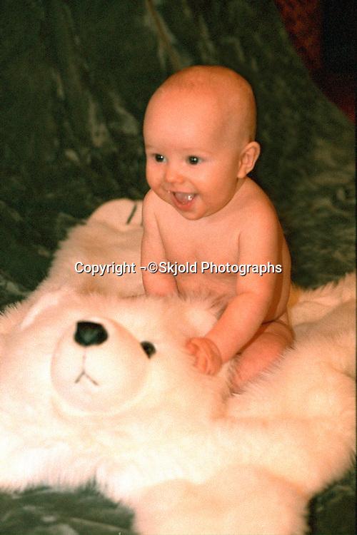 Baby boy smiling happily sitting on stuffed polar bear rug.  St Paul Minnesota USA