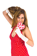 Seductive Young Woman in her twenties licks a heart shape lollipop. Isulated on white background