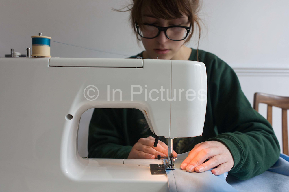 A 17 year-old girl studying the British A-Level Textiles qualificatio, makes her own garment using a family sewing machine. Carefully sewing and stiching the materials together to make her home-made clothing, she allows the needle to travel across the edges, mindful of keeping her fingers away from the shap point that moves fast.
