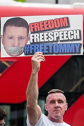 London, UK. 9th June, 2018. A supporter of Tommy Robinson, former leader of the far-right English Defence League, displays a sign to anti-fascists protesting against the March for Tommy Robinson outside Downing Street.