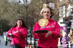 © Licensed to London News Pictures. 09/02/2016. Ilkley, UK. A competitor in this year's pancake race in Ilkley, West Yorkshire, flips her pancake in the dash towards the finish line. The race is held annually in the Yorkshire town of Ilkley on Shrove Tuesday. Photo credit : Ian Hinchliffe/LNP