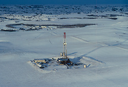 Stock photo of an aerial view of a snow covered on-shore rig drilling site