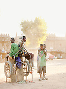 Boys wait for the market to set up in the main square early in the morning , in Djenné, Mali