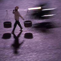Asia, Vietnam, Hanoi, Blurred image of woman carrying traditional baskets along Hoan Kiem Lake in Old Quarter at dusk