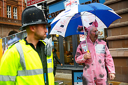 © Licensed to London News Pictures. 06/10/2015. Manchester, UK. A man dressed as a pig demonstrating outside Conservative Party Conference at Manchester Central convention centre on Tuesday, 6 October 2015. Photo credit: Tolga Akmen/LNP