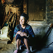 Portrait of Xi Le Li, a Hani ethnic minority woman wearing traditional clothing in Gan Pai Da Zhai village, Yunnan province, China. Costume styles in the past were identified by discrete regions and sub regions, but due to a number of factors some groups are more widely dispersed.  This may be due to migration or search for land, and more recently, as a result of re-settlement of groups by the Chinese government, made necessary by the construction of new roads, reservoirs and hydroelectric schemes. The People's Republic of China recognises 55 ethnic minority groups in China in addition to the Han majority. The ethnic minorities form 9.44% of mainland China and Taiwan's total population and the greatest number can be found in Yunnan Province, 34% (25 ethnic groups).