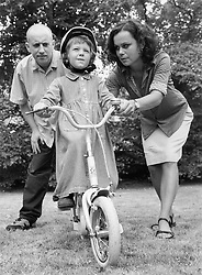 Young girl wearing bike helmet learning to ride bicycle with support of mother and father,