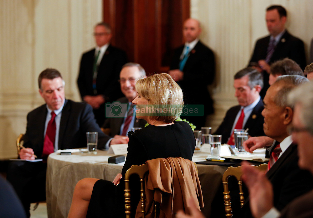 Secretary of Education Betsy DeVos listens to U.S. President Donald Trump at the National Governors Association meeting in the State Dining Room of the White House, Washington, DC, February 27, 2017. (Pool / Aude Guerrucci)