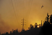 Air Tractor AT-802F fire fighting plane operated by him-Nir Aviation is dropping flame retardant over a large scale forest fire. Photographed in Israel at Sunset
