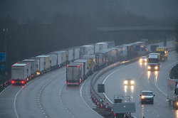 © Licensed to London News Pictures. 21/12/2020. Hollingbourne , UK. Freight traffic being held by police between junctions eight and nine on the M20, Kent. A major police operation is underway in Kent as Operation Stack is implemented on the M20 due to the Port of Dover and Channel Tunnel having to close in response to France closing its borders to the UK.  All freight and passenger traffic have been banned for 48 hours due to the new mutant strain of the Coronavirus in England. traffic. Photo credit:Grant Falvey/LNP