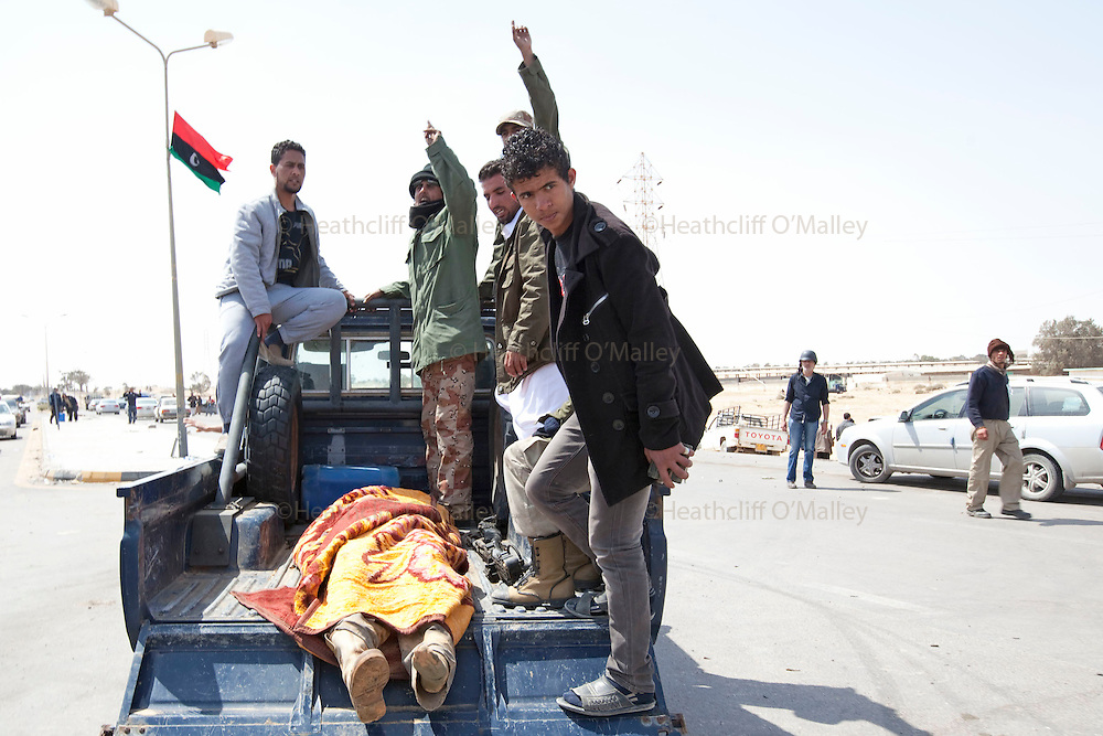 Mcc0030300 . Sunday Telegraph..A dead rebel fighter loaded onto a pickup truck on the road to the town of Ajdabiyah after Libyan government forces retreated on saturday night due to repeated attacks from NATO airstrikes...Ajdabiyah 26 March 2011