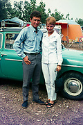 Stylish British couple standing next to their car at a campsite holiday in Spain, 1966