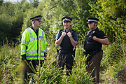 Police officers in a field of baby Christmas trees. Anti-fracking activists join hands to surround the Cuadrilla fracking site. Thousands turned out for a march of solidarity against fracking in Balcombe. The village Balcombe in Sussex is the  centre of fracking by the company Cuadrilla. The march saw anti-fracking movements from the Lancashire and the North, Wales and other communities around the UK under threat of gas and oil exploration by fracking.