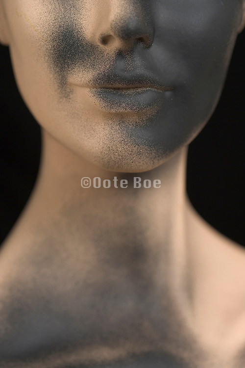 cropped view of a mannequin partly black spray painted