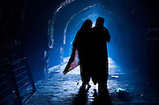 """26th November 2015, New Delhi, India.  Women silhouetted in catacombs of the ruins of Feroz Shah Kotla in New Delhi, India on the 26th November 2015<br /> <br /> PHOTOGRAPH BY AND COPYRIGHT OF SIMON DE TREY-WHITE a photographer in delhi<br /> + 91 98103 99809. Email: simon@simondetreywhite.com<br /> <br /> People have been coming to Firoz Shah Kotla to pray to and leave written notes and offerings for Djinns in the hopes of getting wishes granted since the late 1970's. Jinn, jann or djinn are supernatural creatures in Islamic mythology as well as pre-Islamic Arabian mythology. They are mentioned frequently in the Quran  and other Islamic texts and inhabit an unseen world called Djinnestan. In Islamic theology jinn are said to be creatures with free will, made from smokeless fire by Allah as humans were made of clay, among other things. According to the Quran, jinn have free will, and Iblīs abused this freedom in front of Allah by refusing to bow to Adam when Allah ordered angels and jinn to do so. For disobeying Allah, Iblīs was expelled from Paradise and called """"Shayṭān"""" (Satan).They are usually invisible to humans, but humans do appear clearly to jinn, as they can possess them. Like humans, jinn will also be judged on the Day of Judgment and will be sent to Paradise or Hell according to their deeds. Feroz Shah Tughlaq (r. 1351–88), the Sultan of Delhi, established the fortified city of Ferozabad in 1354, as the new capital of the Delhi Sultanate, and included in it the site of the present Feroz Shah Kotla. Kotla literally means fortress or citadel."""
