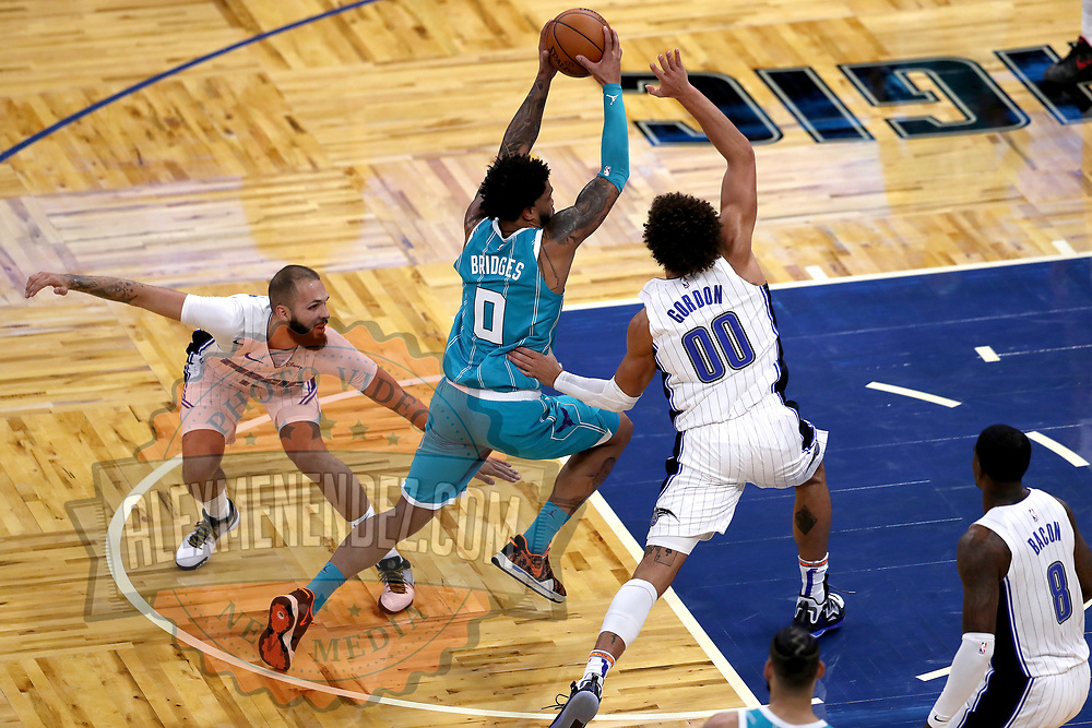 ORLANDO, FL - DECEMBER 17:  Miles Bridges #0 of the Charlotte Hornets drives to the net against Aaron Gordon #00 of the Orlando Magic and Evan Fournier #10 of the Orlando Magic at Amway Center on December 17, 2020 in Orlando, Florida. NOTE TO USER: User expressly acknowledges and agrees that, by downloading and or using this photograph, User is consenting to the terms and conditions of the Getty Images License Agreement. (Photo by Alex Menendez/Getty Images)