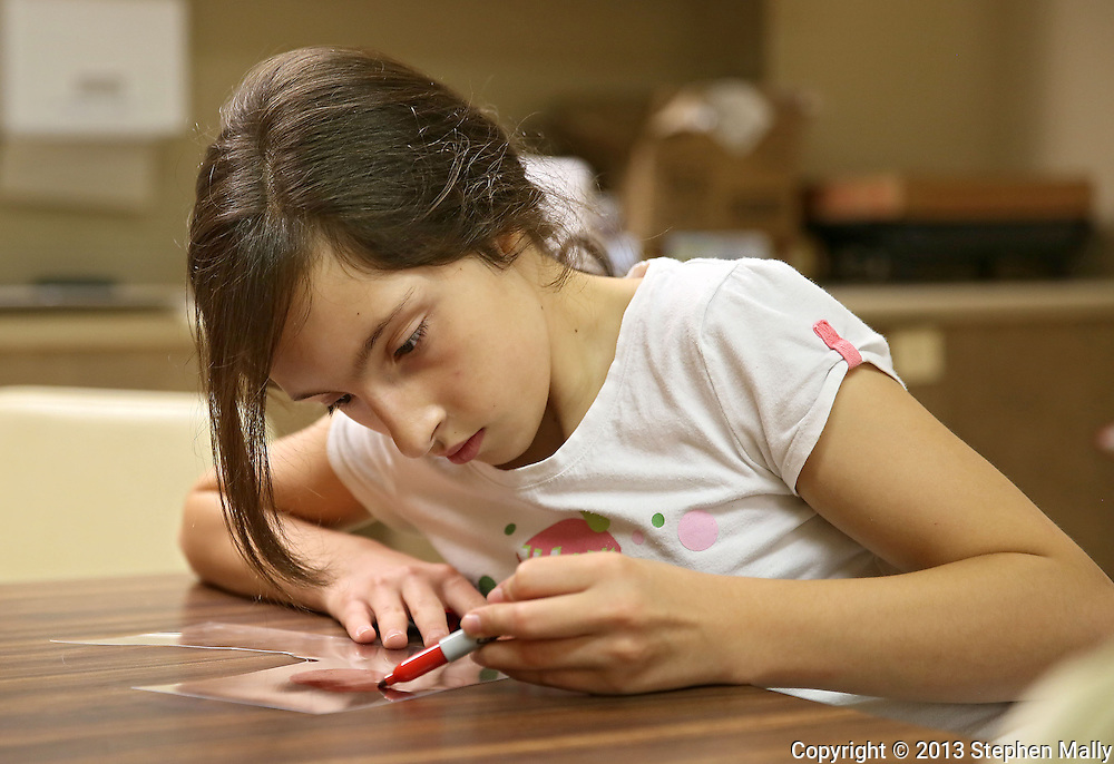 Laela Waddell, 10, of Wellman works on coloring her shrinky dinks craft during a summer camp hosted by the Iowa School for the Deaf at the Iowa Braille and Sight Saving School in Vinton on Tuesday, July 16, 2013.