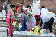 A Mexican family decorates the gravesite of relatives for Day of the Dead festival known in spanish as Día de Muertos at the old cemetery October 31, 2013 in Xoxocotlan, Mexico. The festival celebrates the lives of those that died.