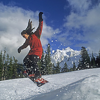 Amy Howat (MR) snowboards over a jump at Mount Baker Ski Area, Washington. Mount Shuksan rises in the backround.