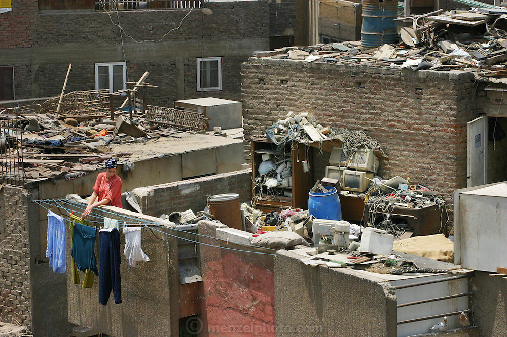 A woman hangs up laundry to dry on a Cairo, Egypt rooftop in old Cairo. Rooftops often end up as repositories for discarded items.