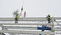 """Ethan Chalke and Jim Johnson of American Steele set the final beam with signatures of the people who have had a significant role in the project during the traditional """"Topping Off"""" ceremony at the Gilford Marine Patrol building on Monday morning.  (Karen Bobotas/for the Laconia Daily Sun)"""