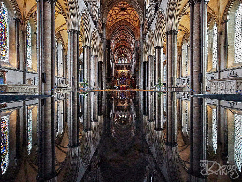 Reflections of stained glass windows and gothic arches in the Font, designed by William Pye, at Salisbury Cathedral.<br /> Salisbury, Wiltshire, UK