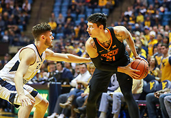 Jan 12, 2019; Morgantown, WV, USA; Oklahoma State Cowboys guard Lindy Waters III (21) holds the ball while guarded by West Virginia Mountaineers guard Chase Harler (14) during the first half at WVU Coliseum. Mandatory Credit: Ben Queen-USA TODAY Sports