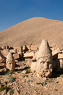 Statue head of Herakles & Apollo (behind) in front of the stone pyramid 62 BC Royal Tomb of King Antiochus I Theos of Commagene, west Terrace, Mount Nemrut or Nemrud Dagi summit, near Adıyaman, Turkey .<br /> <br /> If you prefer to buy from our ALAMY PHOTO LIBRARY  Collection visit : https://www.alamy.com/portfolio/paul-williams-funkystock/nemrutdagiancientstatues-turkey.html<br /> <br /> Visit our CLASSICAL WORLD HISTORIC SITES PHOTO COLLECTIONS for more photos to download or buy as wall art prints https://funkystock.photoshelter.com/gallery-collection/Classical-Era-Historic-Sites-Archaeological-Sites-Pictures-Images/C0000g4bSGiDL9rw