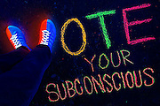 """Blacklight photography of glowing shows that form the shape of the letter V in a chalk drawing that spells """"Vote Your Subconscious""""."""