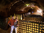 "Calistoga, California.In the wine cave of one of Napa Valley's oldest wineries, Schramsberg Vineyards. Napa Valley, California. A cellar worker will gently knock or ""riddle"" the collected sediment, which has settled in the necks of the countless wine bottles in the Schramsberg wine cave, one of the oldest in Napa Valley, California. Though it is a tedious process, riddling is a fundamental step in the time consuming production of sparkling wine."