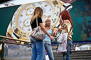 Moscow, Russia, 16/07/2006..Fashionably dressed young Russian women in front of giant advertisement for Rolex watches by Manezh shopping mall  Manezh Square overlooking the Kremlin and Red Square.