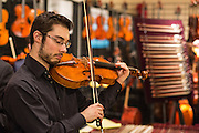A member of the staff at Paul Dulude, a Boston dealer in violins, plays.