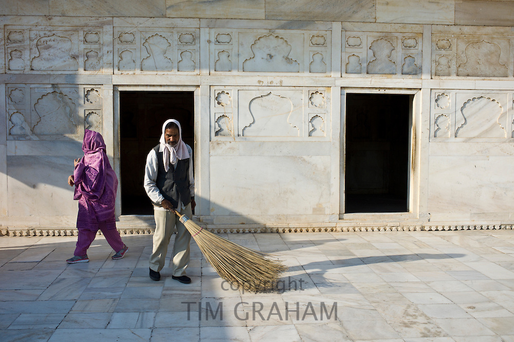 Man sweeping floor at Khas Mahal Palace built 17th Century by Mughal Shah Jehan for his daughters inside Agra Fort, India