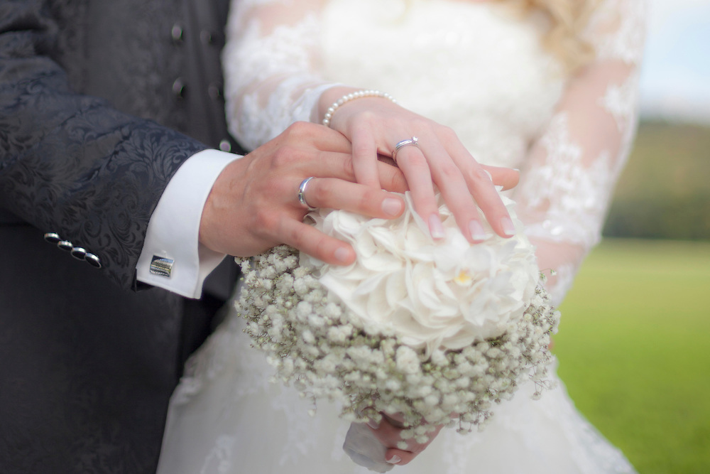 Mid section view of a bride and groom holding bouquet and showing their wedding ring, Ammersee, Upper Bavaria, Bavaria, Germany