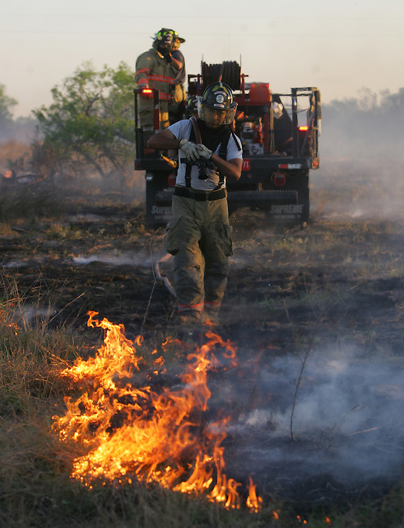 San Manuel, TX - 19 Mar 2008 -.Edcouch Fire Department firefighter Johnny Gonzalez carries a hose to extinguish a fire line on a ranch north of FM 1017 on Wednesday morning..Photo by Alex Jones / ajones@themonitor.com