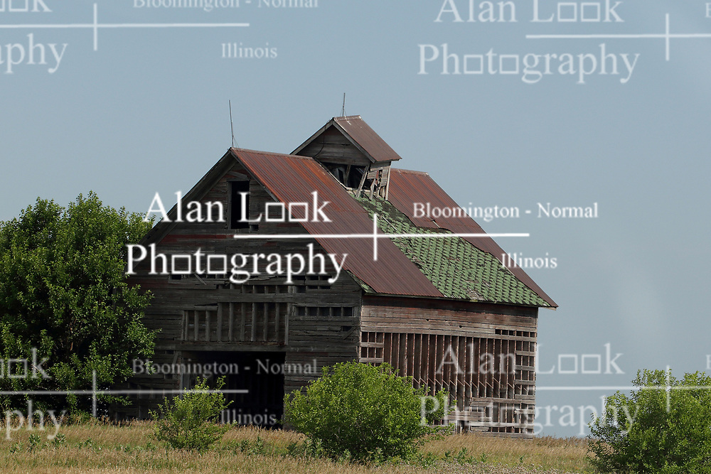old abandoned corn crib and barn stands in deserted barn lot with lightning rods still attached but the roof in bad need of repair