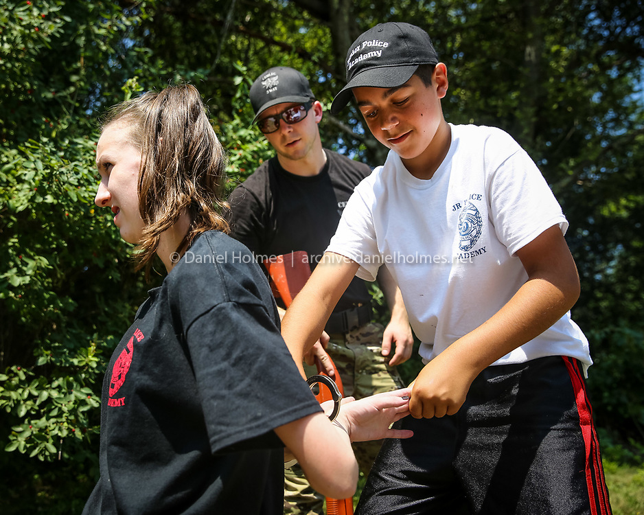 (7/23/14, SOUTHBOROUGH, MA) Emerson Chapski, 15, of Southborough, plays the role of a suspect and is handcuffed by Brendan Hermanspan, 12, of Southborough, with the help of officer Mike Whelan during the Junior Police Academy at the Trottier School in Southborough on Wednesday. Daily News and Wicked Local Photo/Dan Holmes