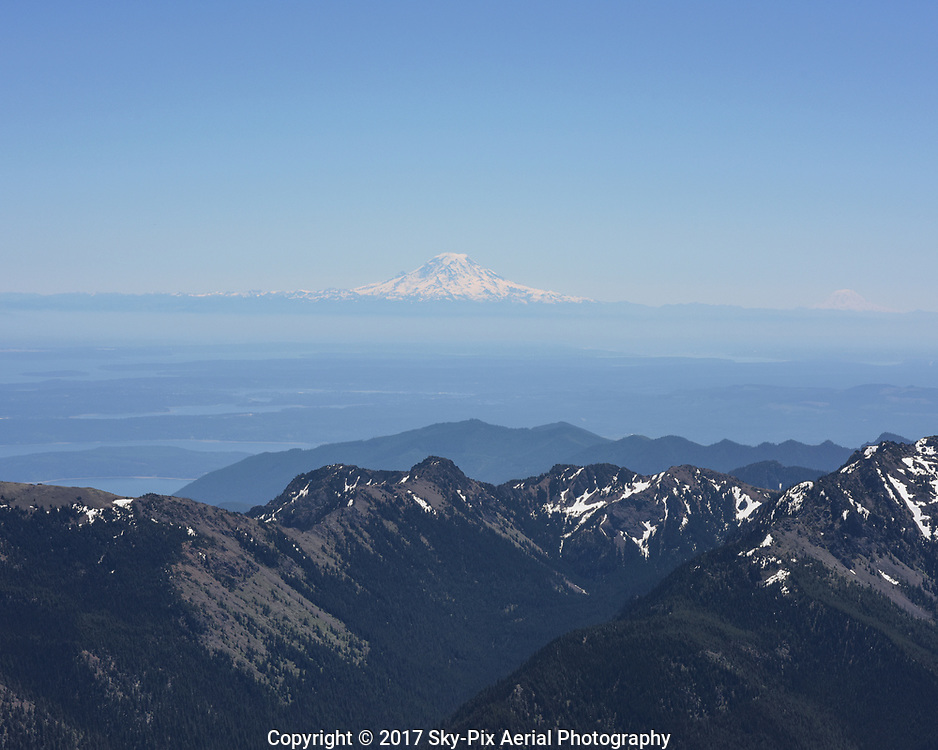 Aerial view taken from over the Olympic Mountains looking toward Mt Rainier with Mt Adams in the distance.