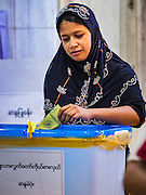 08 NOVEMBER 2015 - YANGON, MYANMAR:  A Muslim woman drops her completed ballot into the ballot box in central Yangon. The citizens of Myanmar went to the polls Sunday to vote in the most democratic elections since 1990. The National League for Democracy, (NLD) the party of Aung San Suu Kyi is widely expected to get the most votes in the election, but it is not certain if they will get enough votes to secure an outright victory. The polls opened at 6AM. In Yangon, some voters started lining up at 4AM and lines were reported to long in many polling stations in Myanmar's largest city. Myanmar's treatment of its Muslim minority has emerged an issue in this election. None of the major parties fielded Muslim candidates.     PHOTO BY JACK KURTZ