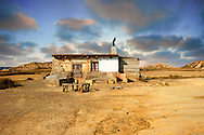 Shack in the Bardena Blanca area of the Bardenas Riales Natural Park, Navarre, Spain . The Bardenas Reales (sometimes referred as Bárdenas Reales) is a semi-desert natural region, or badlands, of some 42,000 hectares (420 km2; 104,000 acres) in southeast Navarre (Spain). The soils are made up of clay, chalk and sandstone and have been eroded by water and wind creating surprising shapes, canyons, plateaus, tabular structures and isolated hills, called cabezos. Bardenas Reales lacks urban areas, vegetation is scarce and the many streams that cross the territory have a markedly seasonal flow, staying dry most of the year.<br /> <br /> Visit our SPAIN HISTORIC PLACES PHOTO COLLECTIONS for more photos to download or buy as wall art prints https://funkystock.photoshelter.com/gallery-collection/Pictures-Images-of-Spain-Spanish-Historical-Archaeology-Sites-Museum-Antiquities/C0000EUVhLC3Nbgw